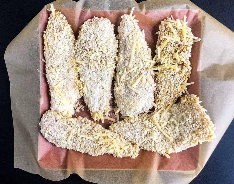 Breaded tenders on a parchment lined plate ready to rest in the refrigerator.