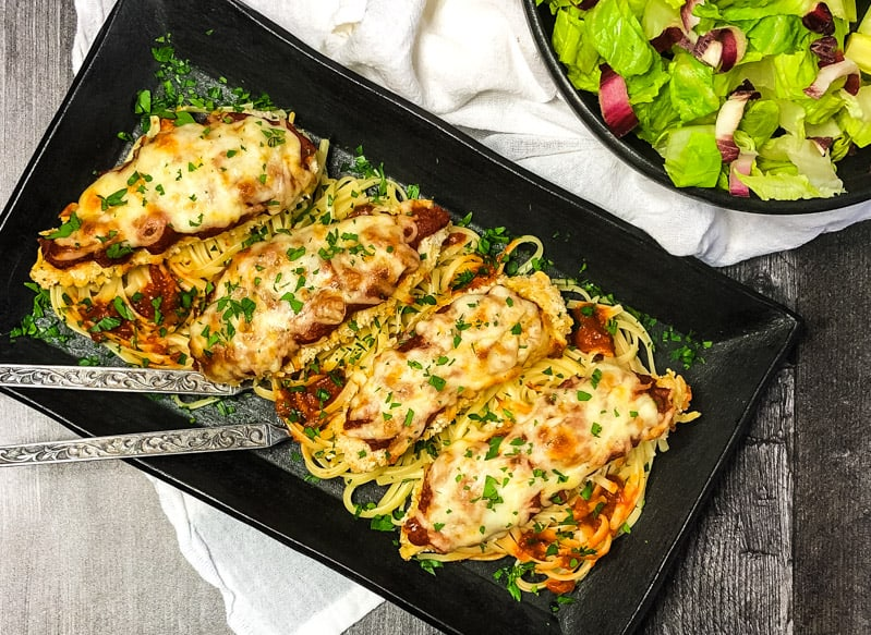 Overhead shot of Chicken Parmesan resting on linguine on a black serving platter with a salad to the side.