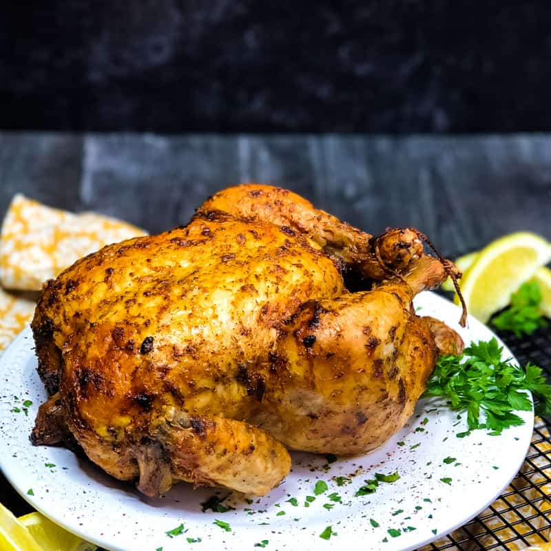 Air Fryer Whole Chicken on a white plate with parsely and lemon garnish.