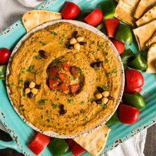 Overhead shot of Chipotle Black Bean Hummus with red and green peppers and toasted flatbread.