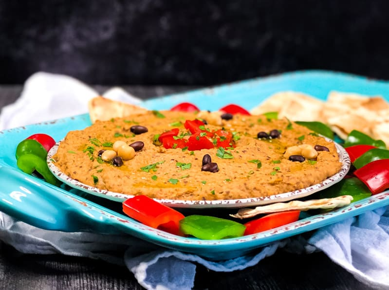 Side view of Chipotle Black Bean Hummus garnished with red and green peppers and toasted flatbread.