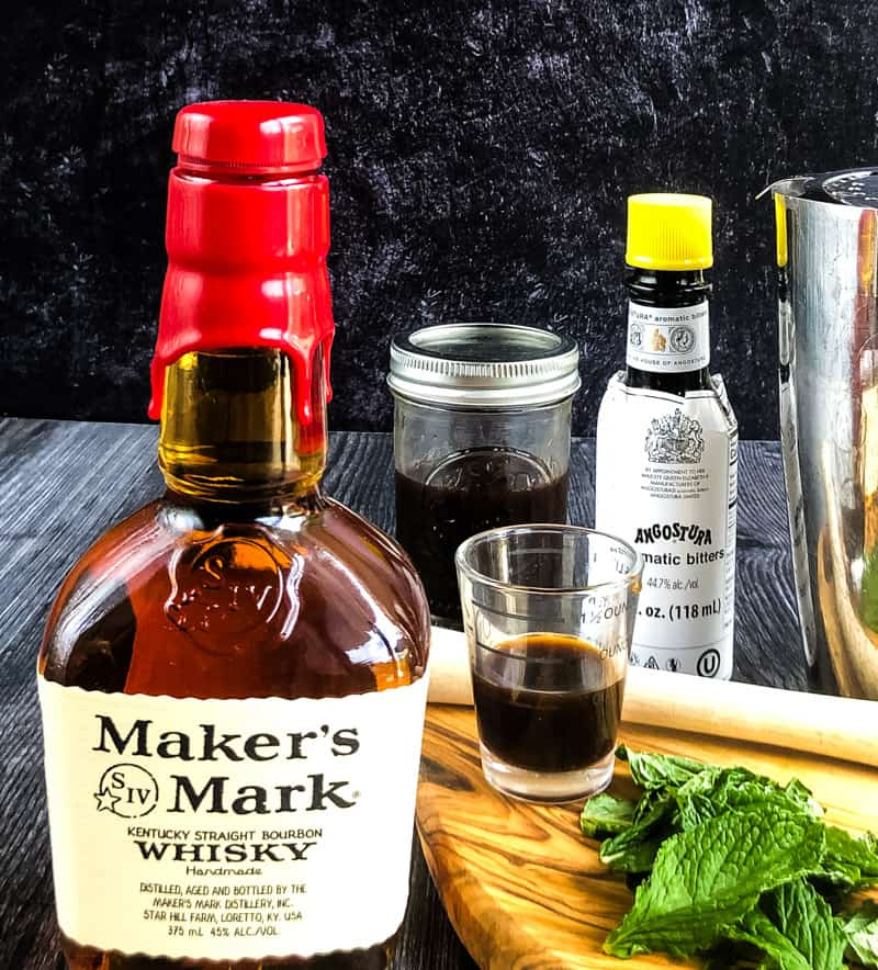 The indredients (bourbon, simple syrup, mint, and bitters) gathered together