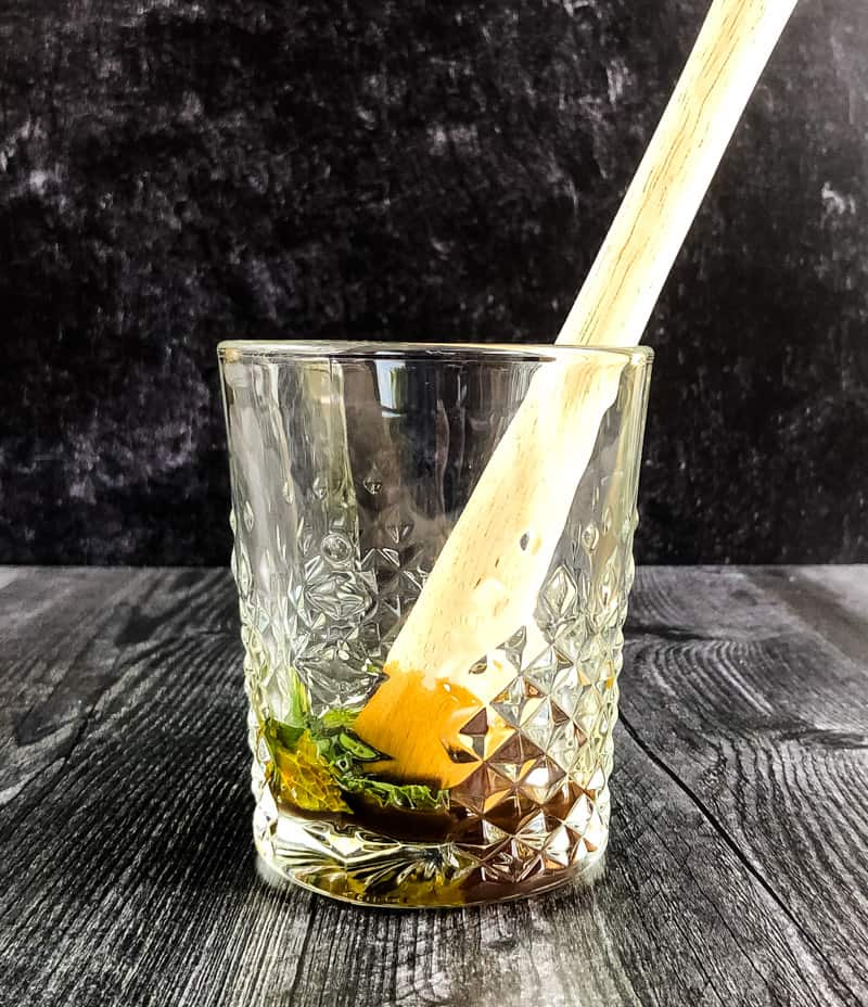 Rocks glass with a wood muddler with mint and simply syrup in the bottom.