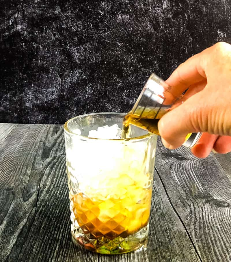Pouring bourbon over crushed ice into a rocks glass