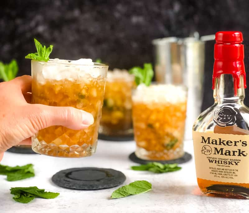 A cheers shot with additional Mint Juleps, cocktail shaker, and bottle of Maker's Mark blurred in background.