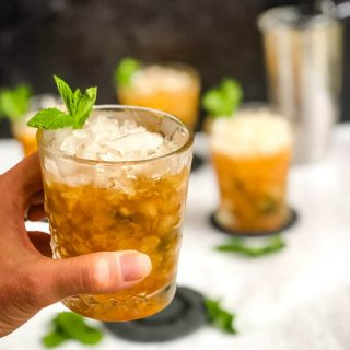 Close up of Mint Julep with additional cocktails and shaker blurred in background.