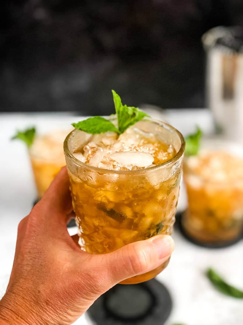 Close up of Mint Julep with additional cocktails blurred in the background.