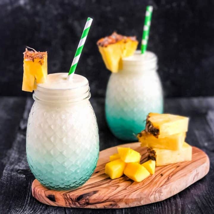 Creamy Mango Colada next to pineapple and mango garnish with a second cocktail blurred in the background.