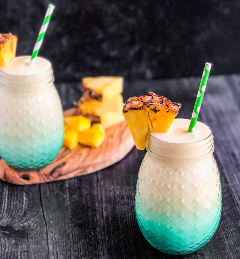 Close up of Mango Colada garnished with a fresh pineapple triangle with second cocktail blurred in the background.