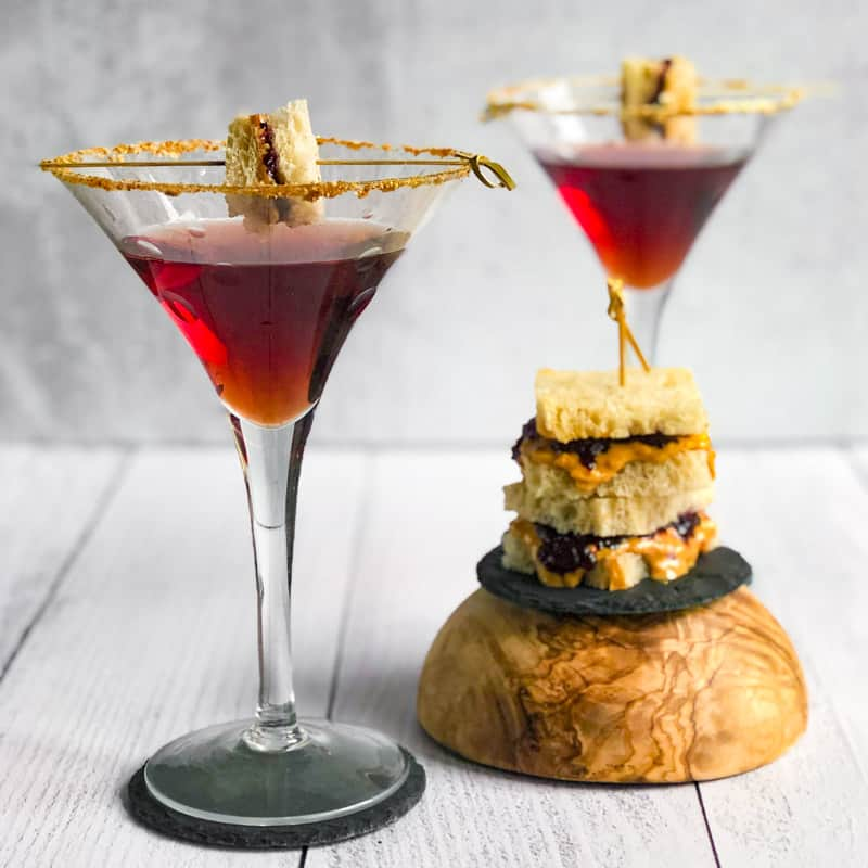 Peanut Butter and Jelly Martinis with a small stack of peanut butter and jelly sandwiches.