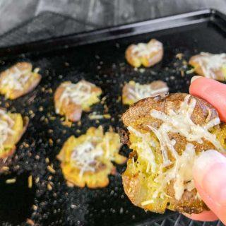 Close up of hand holding Smash Potato above sheet pan of potatoes.