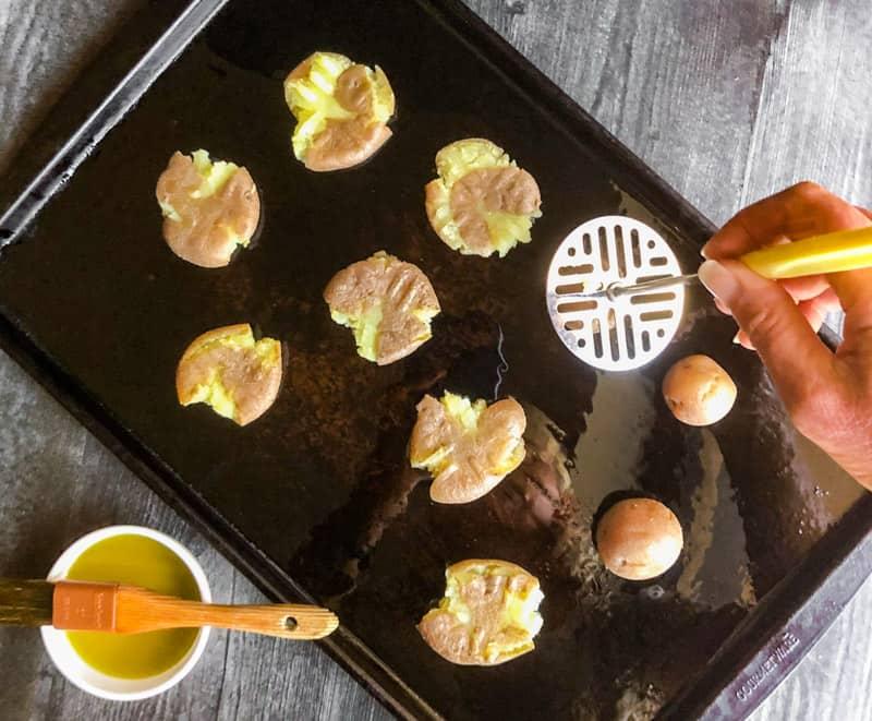 Smashing the potatoes on the sheet pan