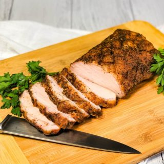 Close up of half of pork loin sliced on a wooden cutting board with knife in front garnished with parsely