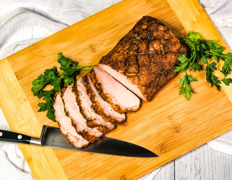 Overhead shot of pork loin half sliced on a wooden cutting board with knife under slices and garnished with parsley