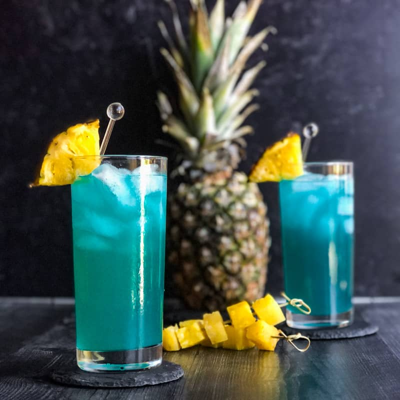 Blue Hawaiian garnished with fresh pineapple wedges with a pineapple in the background.