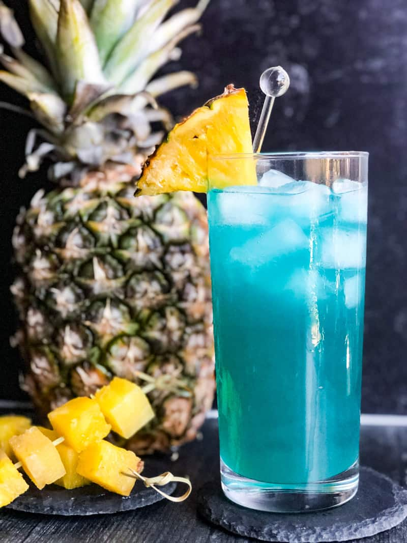 Close up shot of Blue Hawaiian garnished with fresh pineapple wedges with a pineapple in the background.