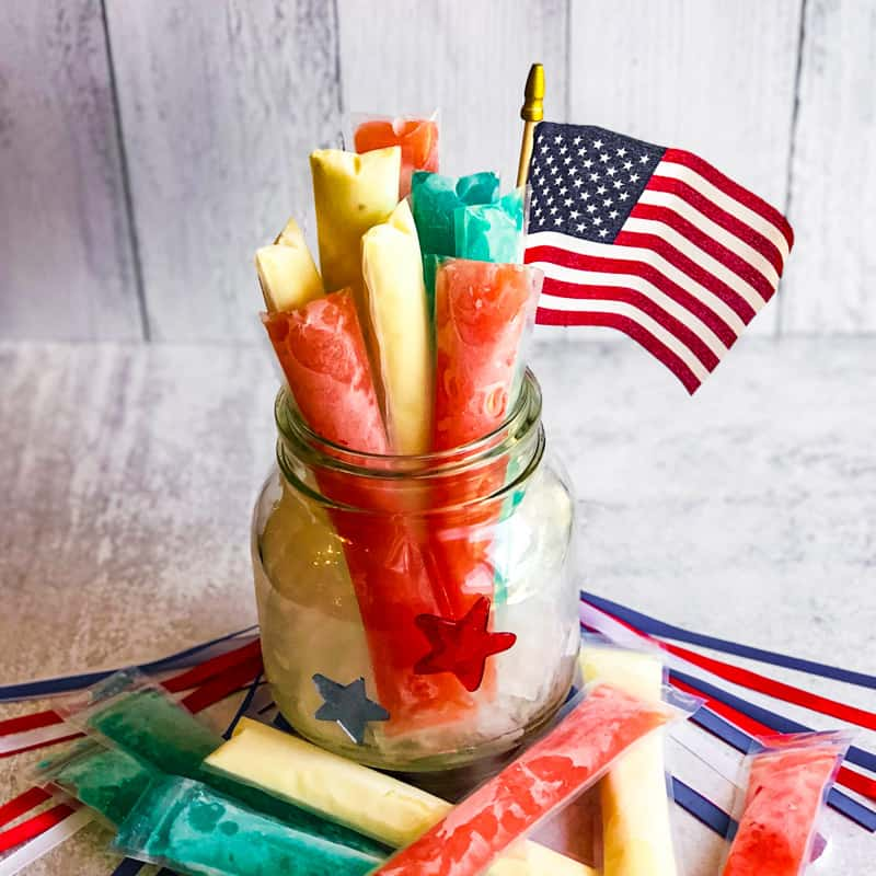 Red, white, and blue poptails in a glass jar with more poptails scattered around table.