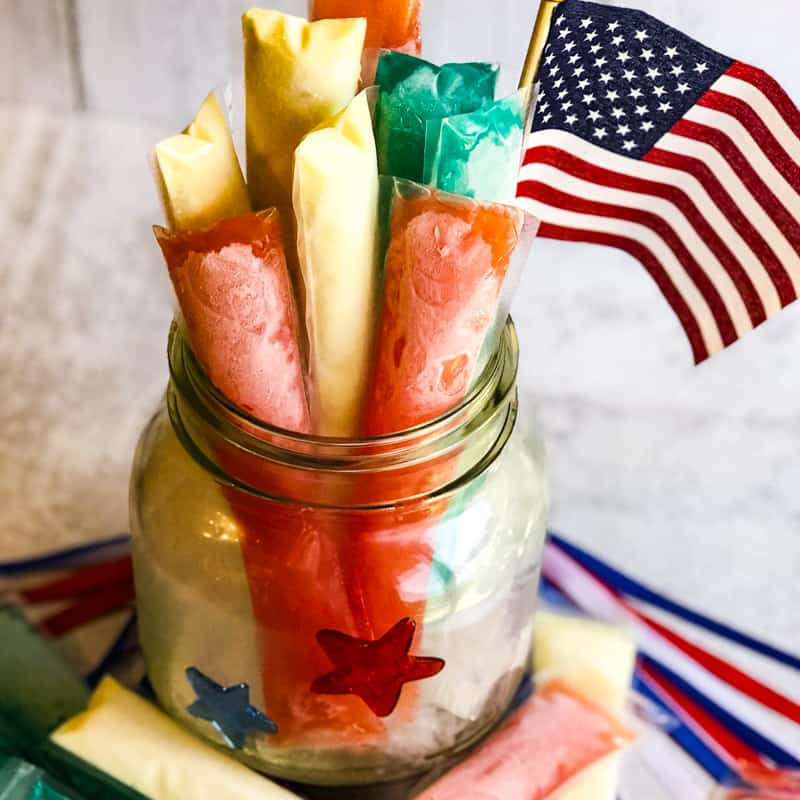 Close up of Boozy Freeze Pops in a large glass jar full of ice garnished with an American flag.