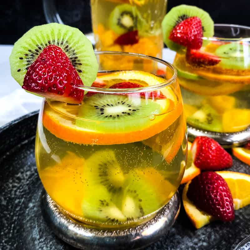 Close up of glass of White Wine Sangria with second glass and pitcher blurred in background; garnished with strawberries, kiwi, and orange slices.