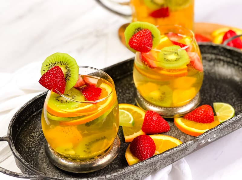 Two glasses of White Wine Sangria on a metal tray garnished with strawberries and orange and lime slices; blurred pitcher in background.