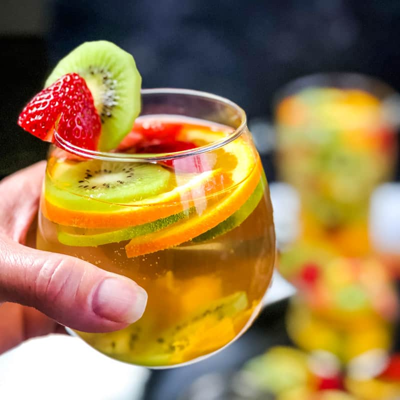 Hand holding a glass of White Wine Sangria with blurred cocktail and pitcher in the background