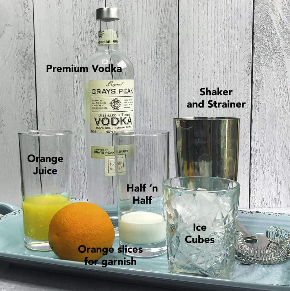 Ingredients for Creamsicle Martini displayed on an aqua colored tray.