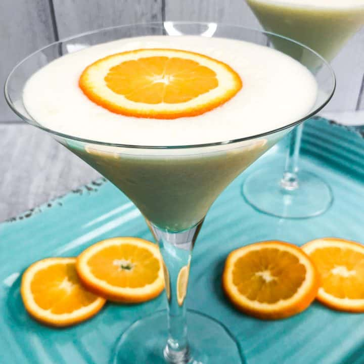 Closeup of Creamsicle Martini on an aqua colored tray with orange slices for garnish and partial martini blurred in the background.