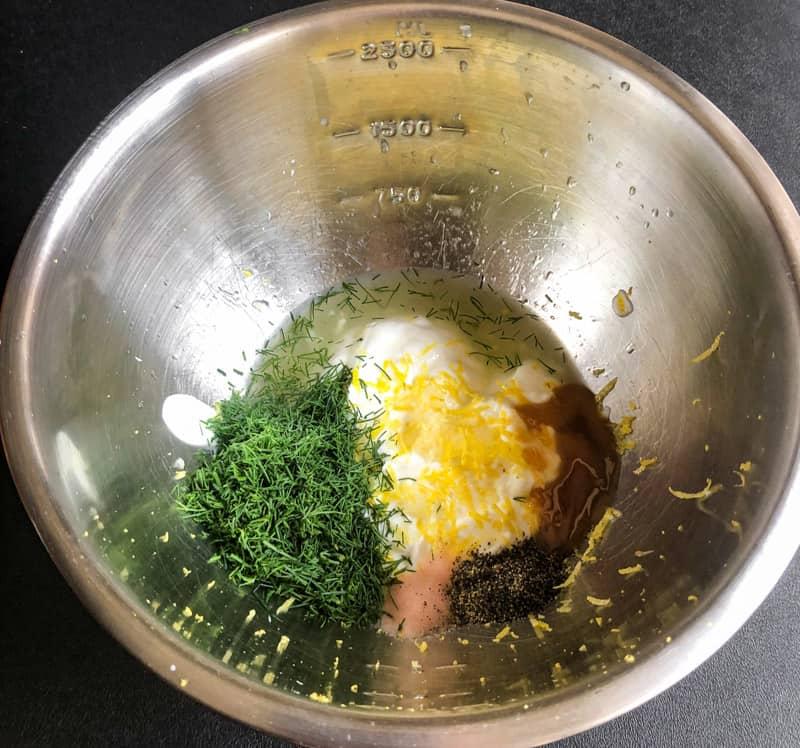 Dressing ingredients: Greek yogurt, chopped dill, lemon juice, vinegar, honey, salt and pepper in a stainless steel bowl.