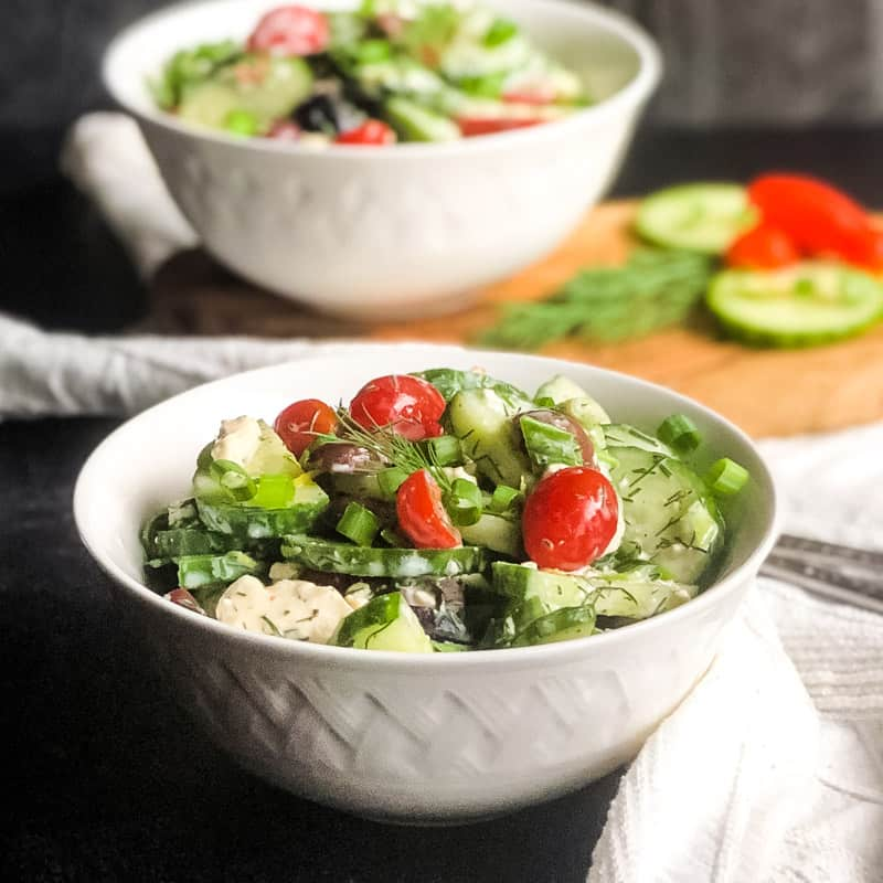 Close up of Greek Inspired Cucumber Salad with partial second bowl next to chopped cucumber, tomato, and dill, blurred in background.