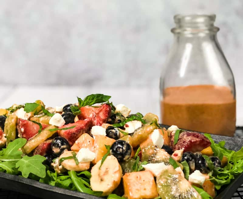 Close up of Tropical Fruit Salad on a bed of arugula on a black serving platter with bottle of dressing blurred in the background.