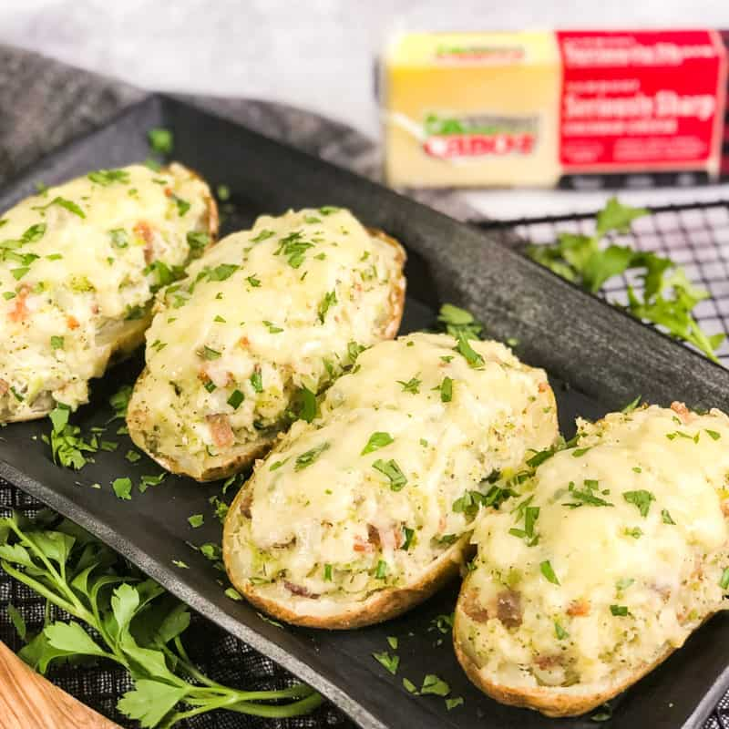 Overhead shot of Air Fryer Twice-Baked Loaded Potatoes garnished with parsley on a black serving platter with a block of Cabot Seriously Sharp Cheddar Cheese in forground.