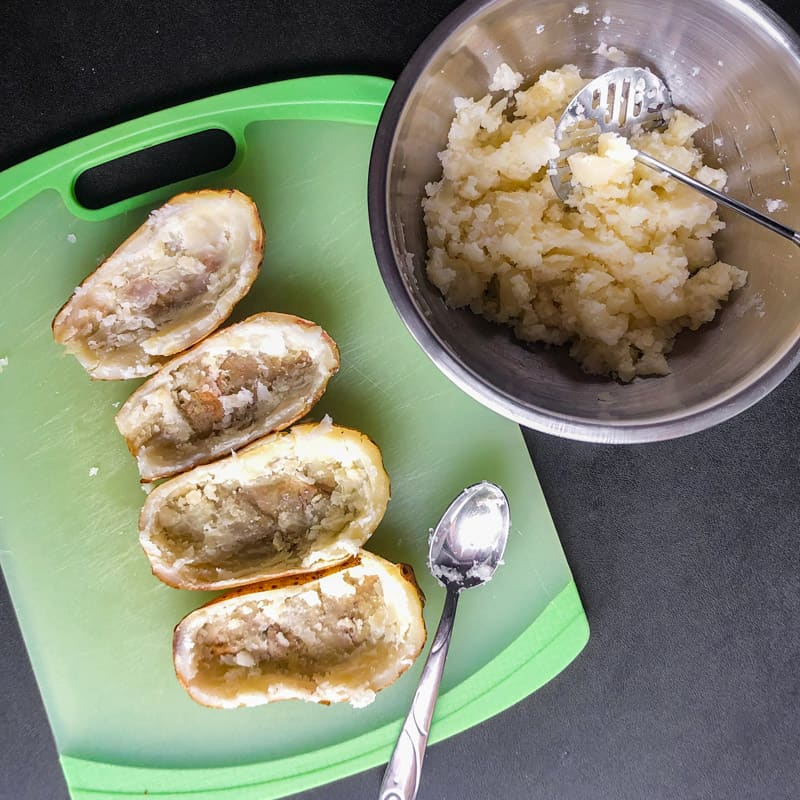Scooped out potato halves on a green cutting board, next to a bowl of the mashed potato flesh.