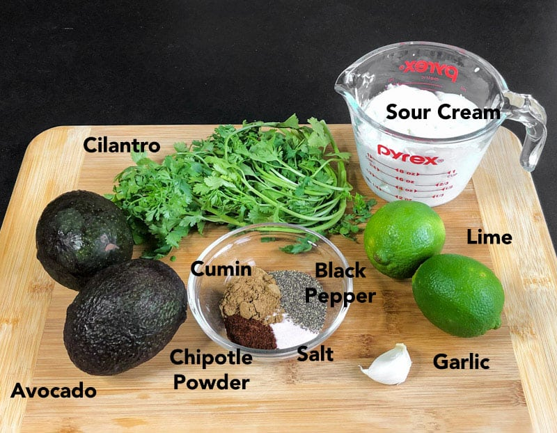 Ingredients for avocado crema on a cutting board, including: avocado, garlic, cilantro, lime, sour cream, and spices.