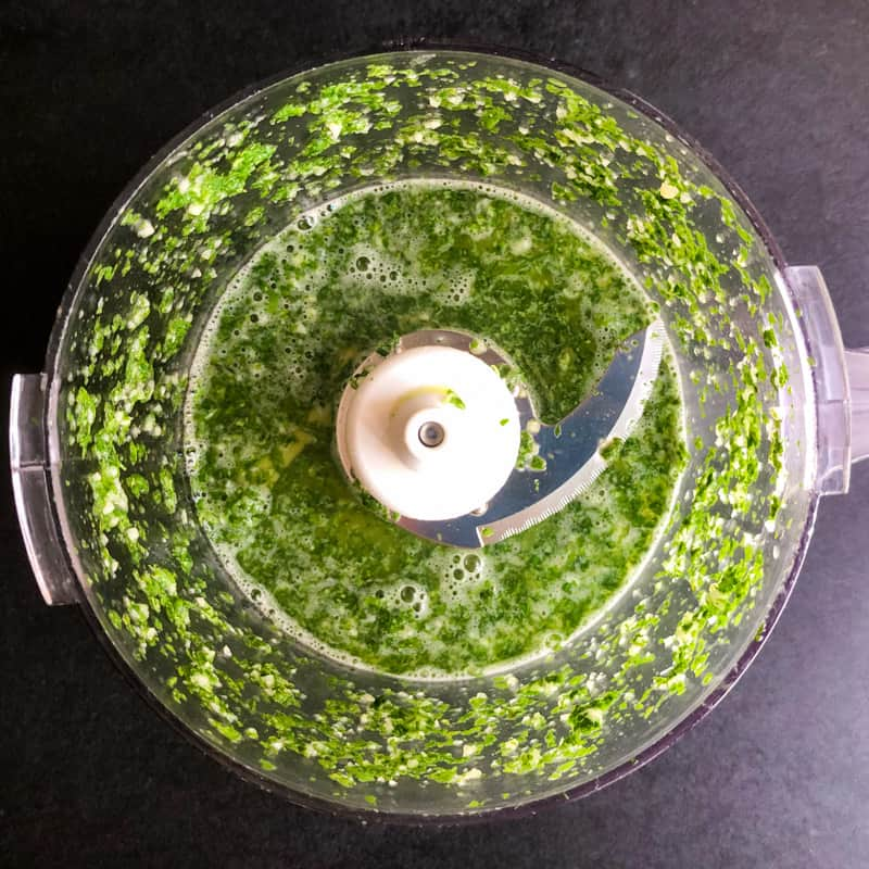 Blended cilantro, lime juice, and garlic in the bowl of a food processor.