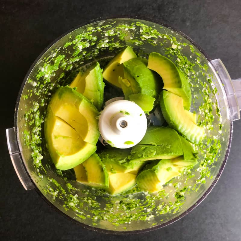 Avocado is added to the cilantro mixture in the food processor.