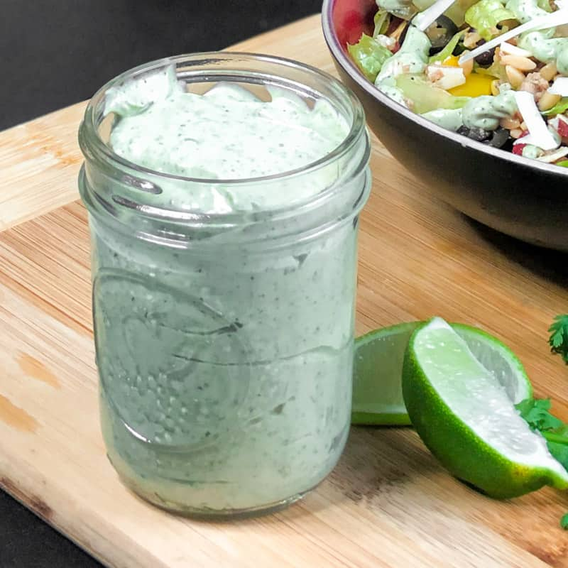 A mason jar of Avocado Crema on a wood cutting board next to a bowl of salad and sliced limes.
