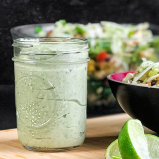 Close up of Avocado Crema in a mason jar with taco salad blurred in the background and sliced limes in the foreground.