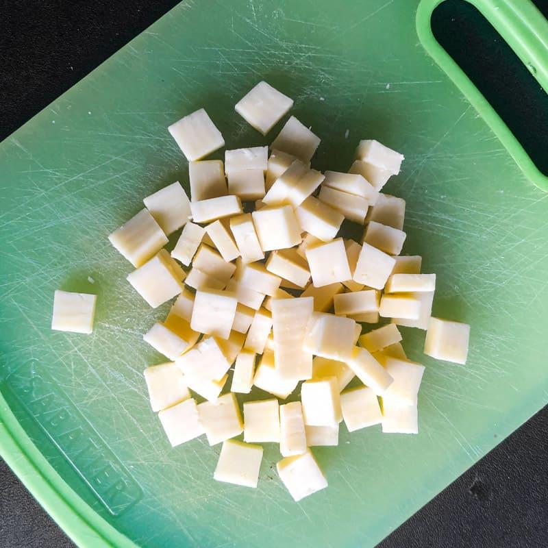 Chunks of cheddar cheese chopped on a green cutting board.
