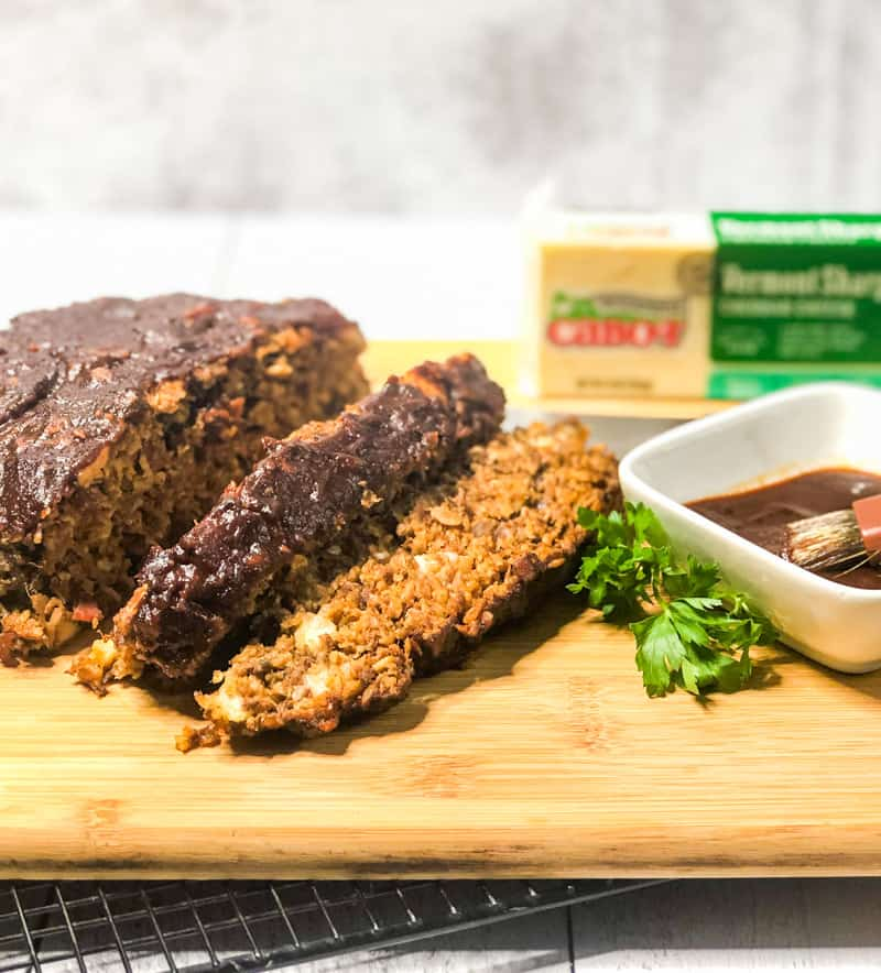Side shot of BBQ Bacon Meatloaf sliced on a wood cutting board with a bowl of barbecue sauce and Cabot Cheese block in background.