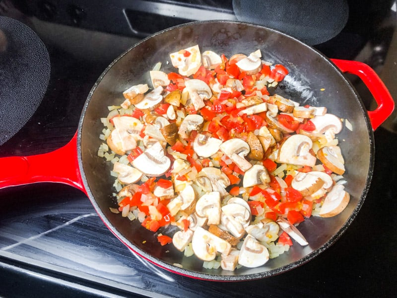 Tomatoes and mushrooms added to the skillet to saute.