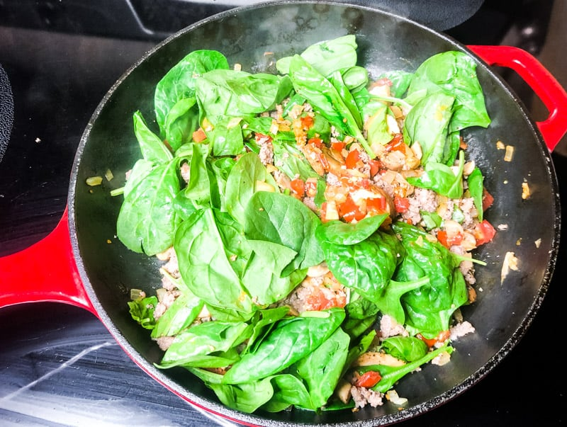 Spinach added to the skillet to wilt with the rest of the vegetables.