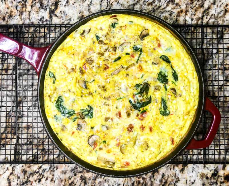 Overhead shot of frittata cooling in the skillet on a wire rack.