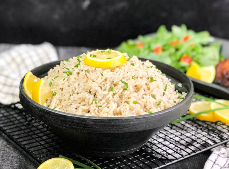 Coconut Rice in a black bowl garnished with chives and lemon with a blurred salad in the background.