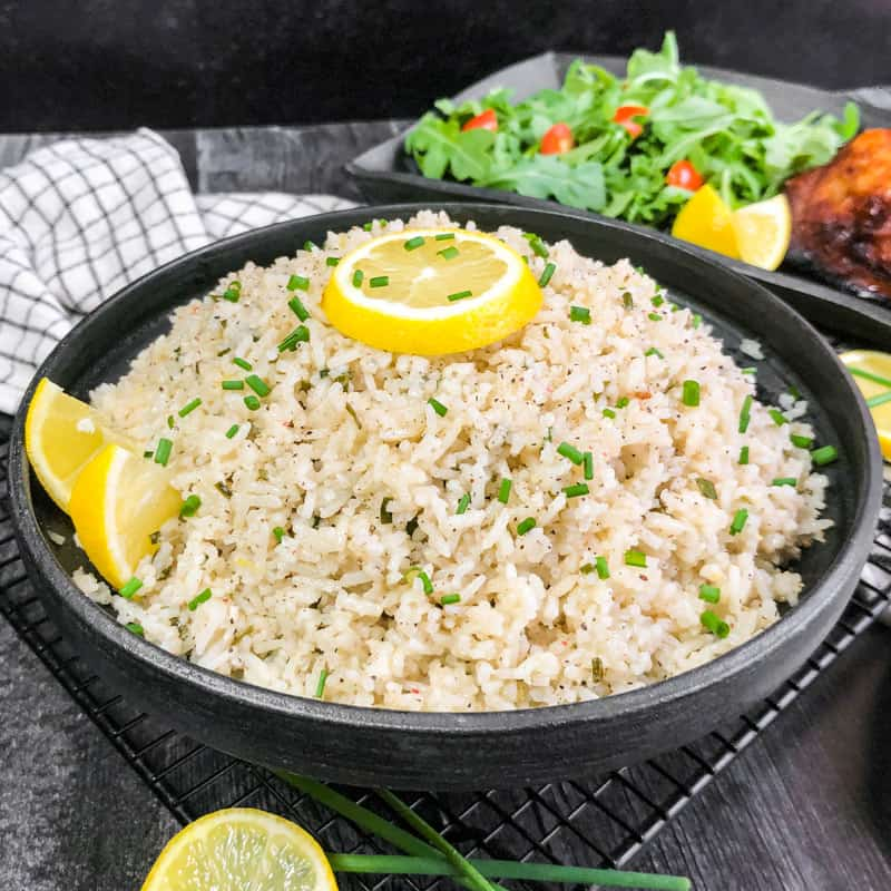 Close up of Coconut Rice in a black bowl, garnished with lemon and fresh chives with a blurred salad and chicken in the background.