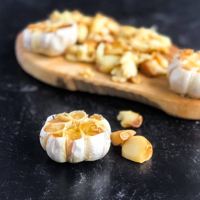 Close up of a head of roasted garlic with cutting board and more garlic heads and cloves blurred in background.