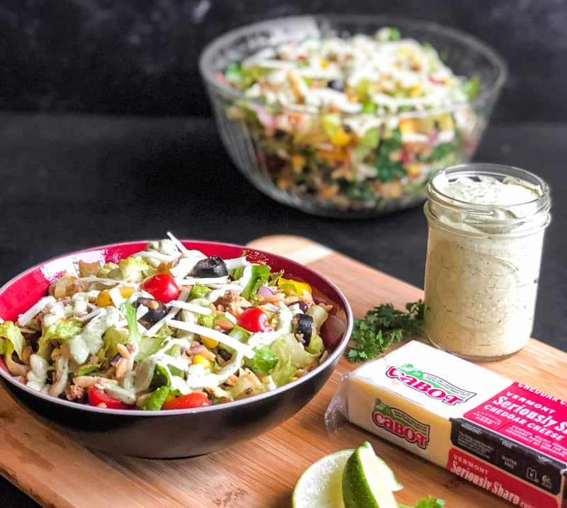 Individual serving of Taco Pasta Salad in a red and black bowl on a wood cutting board with a mason jar of Avocado Crema and a block of Cabot Seriously Sharp Chedar Cheese to the right and large glass bowl of taco salad blurred in the background.