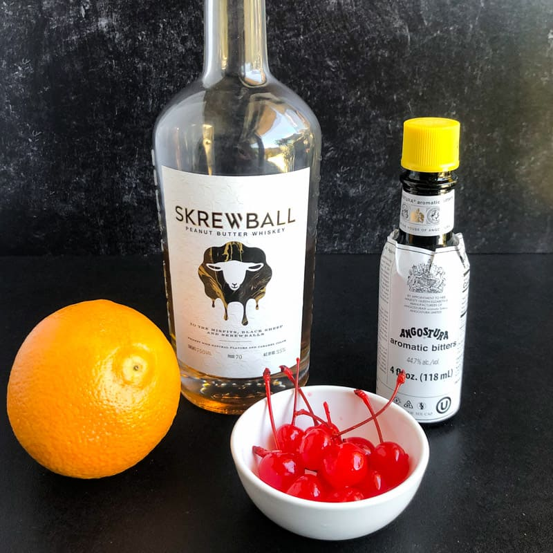 Ingredient shot for Peanut Butter Whiskey Old Fashioned: Skrewball whiskey, Angostura bitters, maraschino cherries, and an orange.