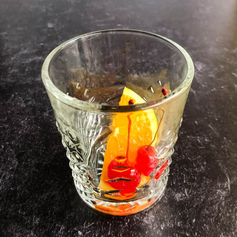 Orange slice and two cherries in a rocks glass.