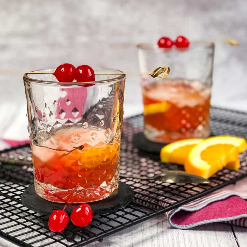 Two old fashioned cocktails on a wire rack garnished with cherries and orange slices.