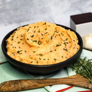 Side shot of Savory Mashed Sweet Potato Blend in a black bowl garnished with fresh chives.
